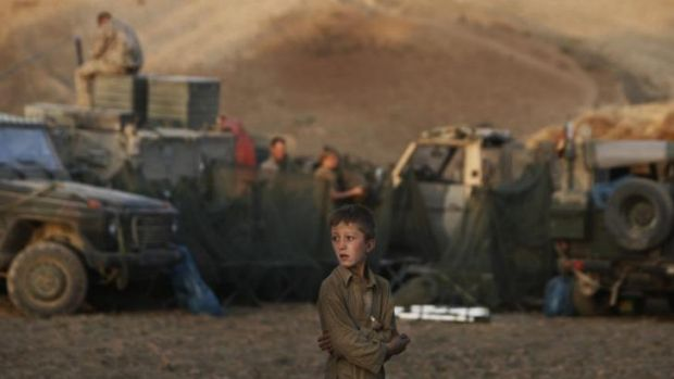 Body of work: An boy looks on as German ISAF soldiers prepare a temporary camp to overnight in during a long term patrol ...