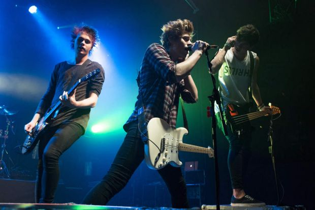 Michael Clifford, Luke Hemmings and Calum Hood of 5 Seconds Of Summer perform on stage at The Ritz, Manchester, United ...