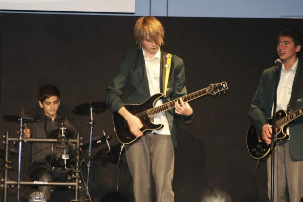 Michael from 5 seconds of summer performs at a school concert.