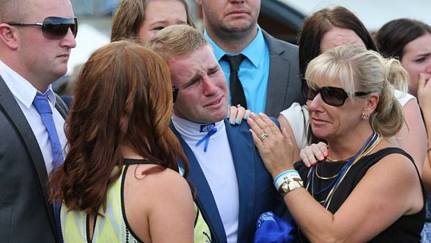 Tommy, comforted by friends and family during the minute's silence.
