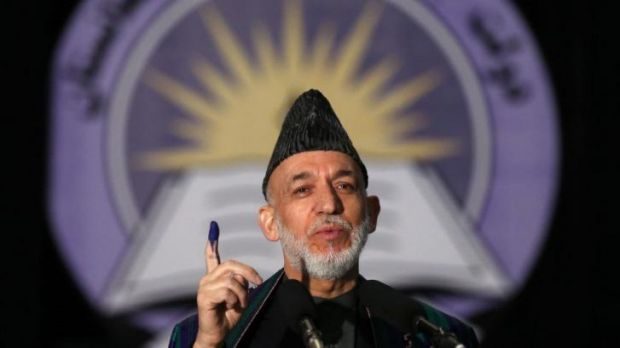 Afghan President Hamid Karzai holds up his inked stained finger after voting.