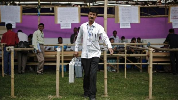 A polling officer carries an electronic voting machine in the Indian state of Assam.