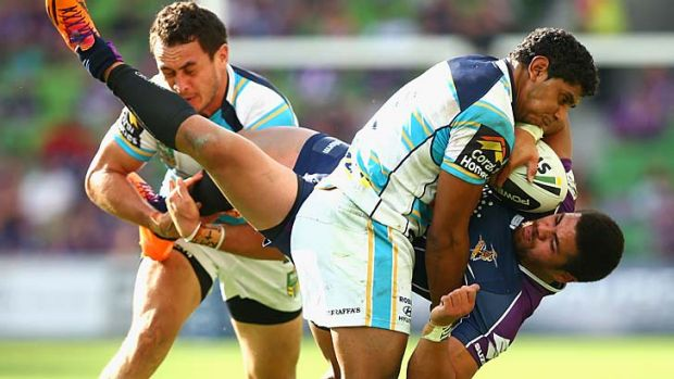 Storm's Young Tonumaipea is greeted by Gold Coast's Brad Takairangi and Albert Kelly.