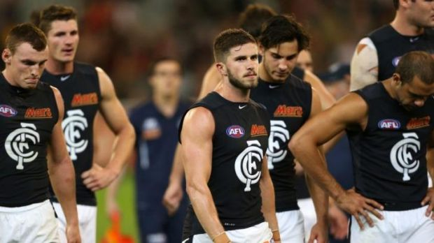 Despondent Carlton captain Marc Murphy walks off with his team after its heavy loss to Essendon