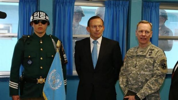 North Korean soldiers stare at Prime Minister Tony Abbott through the window as he tours the T2 hut at the Korean ...