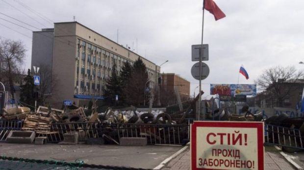 Barricades and Soviet era red and Russian national flags at an entrance to the security service building in Luhansk.