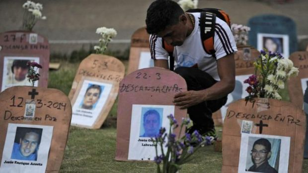 A man arranges tombstones with pictures of dead protesters in Caracas.