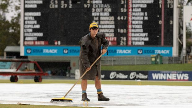 A groundsman sweeps away the rain at Manuka Oval earlier this year.