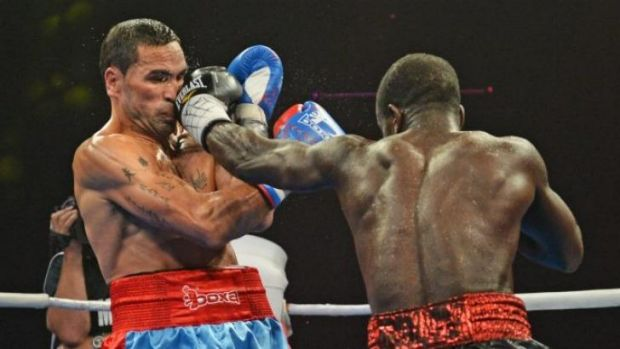 Blow by blow: Joshua Clottey (right) dishes out the punishment to Anthony Mundine.