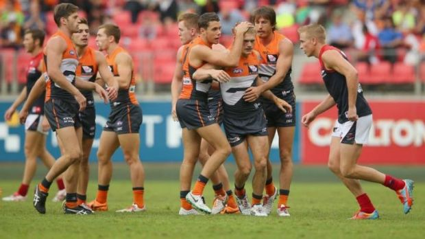 Adam Treloar is congratulated by his team mates after kicking a goal against the Melbourne Demons.