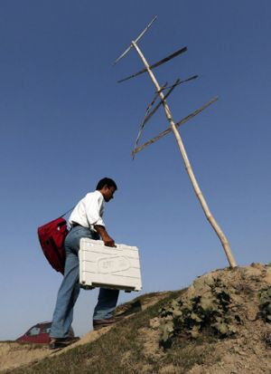 A polling officer carries an electronic voting machine on his way to a polling station in the north-eastern Indian state ...