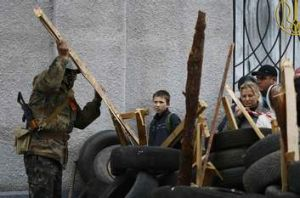 An armed man strengthens a barricade in front of the police headquarters in Slaviansk, April 12, 2014. Pro-Russian ...