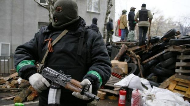 An armed man stands next to a barricade in front of the police headquarters in Slaviansk.