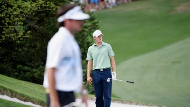 Jordan Spieth of the United States reacts to a bunker shot on the tenth hole as Bubba Watson looks on.