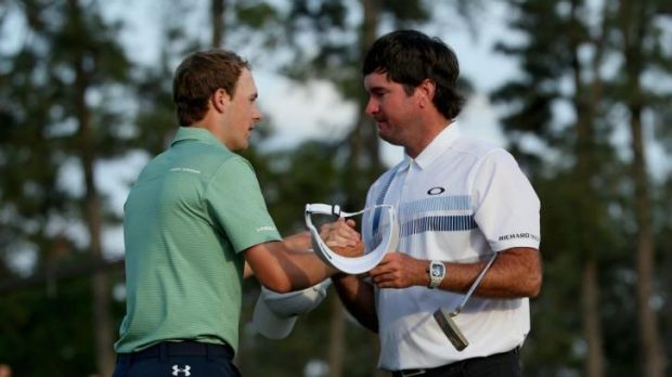 Bubba Watson of the United States shakes hands with Jordan Spieth on the 18th green.