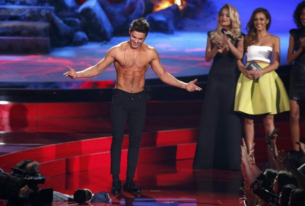 Zac Efron poses after he threw off his shirt as he accepts the award for best shirtless performance for <i>That Awkward ...