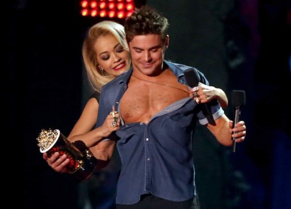 Singer Rita Ora strips actor Zac Efron of his shirt after accepting the best shirtless performance awardat the 2014 MTV ...