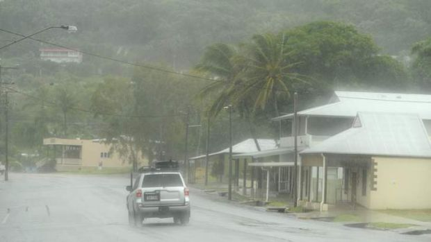 A car drives through torrential rain from Cyclone Ita