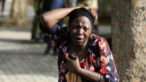 Shock ... A bystander reacts as victims of a bomb blast arrive at the Asokoro General Hospital in Abuja. At least 71 ...