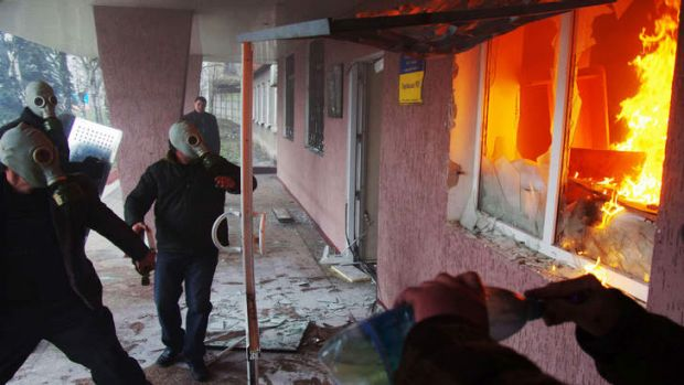 Pro-Russia protesters wearing gas masks storm a regional police building in the eastern Ukrainian city of Horlivka.