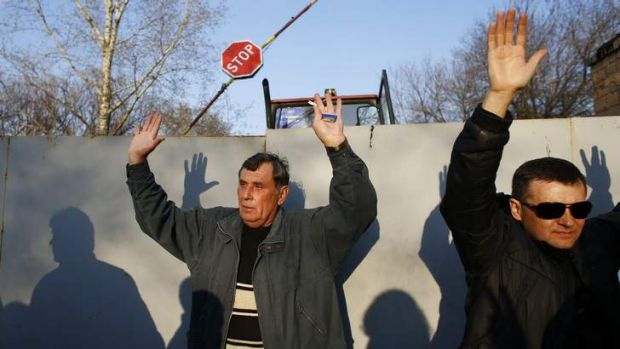 Pro-Russian protesters hold their hands up in the air in Kramatorsk.