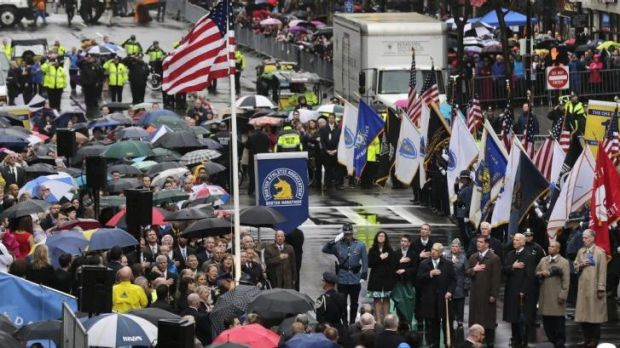 Survivors, families of victims, officials, first responders and guests pause as the flag is raised at the finish line of ...