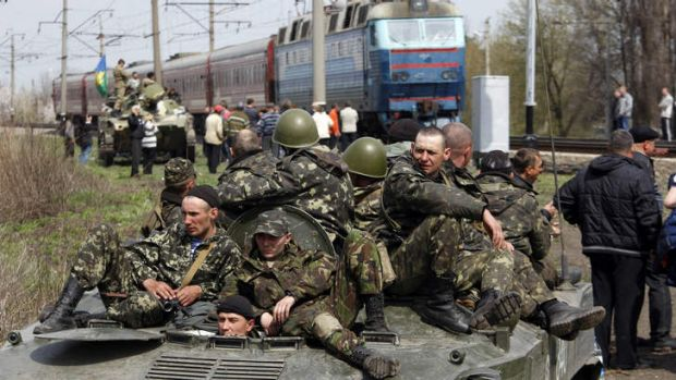 Pro-Russian activists block Ukrainian men riding on armoured combat vehicles.