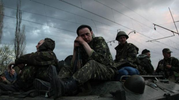 Ukrainian soldiers sit on armoured vehicles as they are blocked by pro-Russian supporters in Kramatorsk.