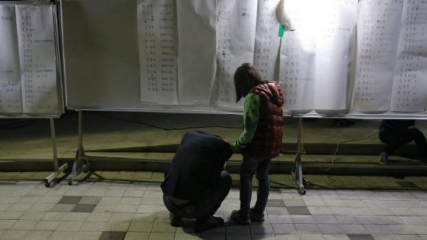 A woman cries after finding her son's name in a list of survivors posted at a gym in Jindo.