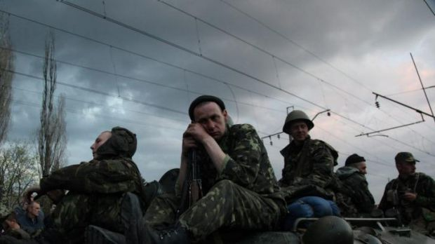 Ukrainian soldiers sit on armoured vehicles as they are blocked by pro-Russian supporters.