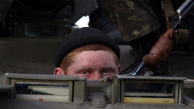 A soldier peeks out from behind a column of vehicles.