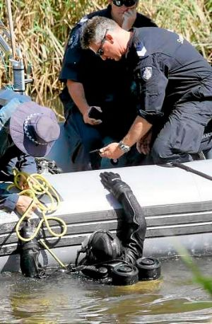 A police diver hands over an object found in a search of the Yarra River in March related to Dimitrios Belias' death.