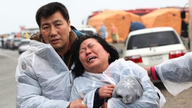 Grief ... a relative of a passenger aboard a sunken ferry weeps at a port in Jindo.