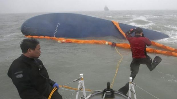Rescue team members next to the capsized  ferry.