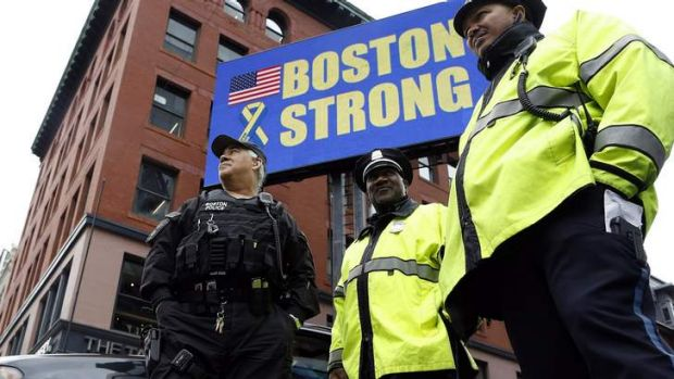 Boston Police stand near the site of one of the two bomb blasts on the one-year anniversary of the Boston Marathon ...