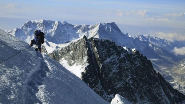 Top of the world: A climber pauses on the way to the summit of Mount Everest. A file photo released by mountain guide ...