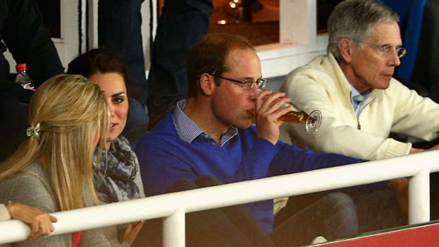Off duty: Prince William enjoys a beer while sitting with Catherine to watch the match between the Waratahs and the ...