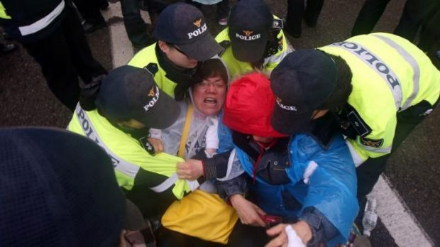 Relatives of missing passengers from the ferry Sewol react as they are blocked from marching by South Korean police on ...