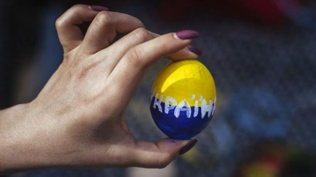 Fragile state: a woman holds an Easter egg painted with the Ukrainian national colours at a rally in the eastern city of ...