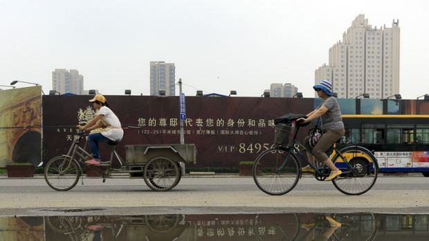 Cyclists ride past newly built residential housing in Beijing, China.