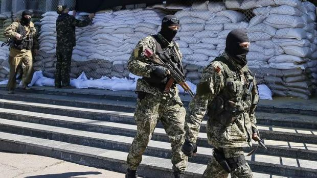 Who are these masked men? Pro-Russian armed men walk past the mayor's office in Slaviansk, Ukraine.