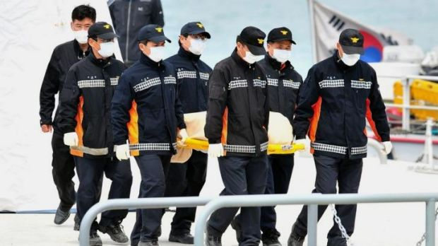 Grim task: South Korea rescue members carry the body of a victim recovered from the ferry to an ambulance.