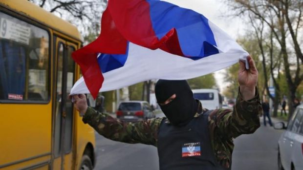 Defying Ukraine's new government ... A masked pro-Russia protester waves the Russian flag in Donetsk, eastern Ukraine.