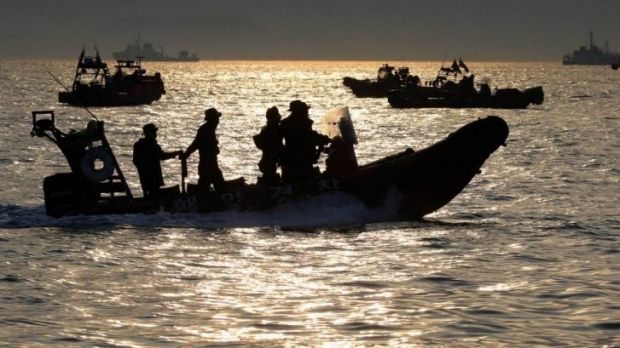 Grim task ... Rescue workers and divers look for people believed to have been trapped in the sunken ferry in water off ...