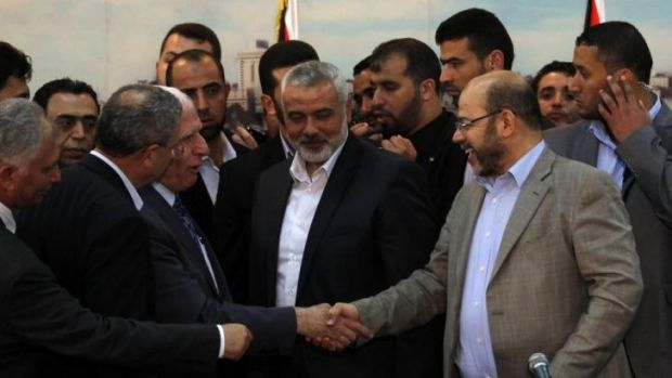 Palestinian Fatah delegation chief Azzam al-Ahmed, left, shakes hands with Hamas deputy leader Musa Abu Marzuk after the ...