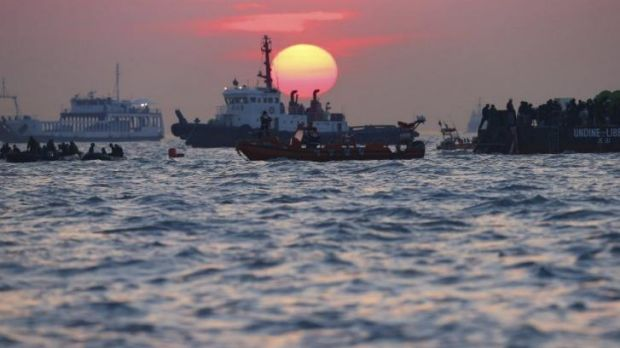 South Korean rescue workers operate during sunset near the site where the capsized ferry Sewol sank.