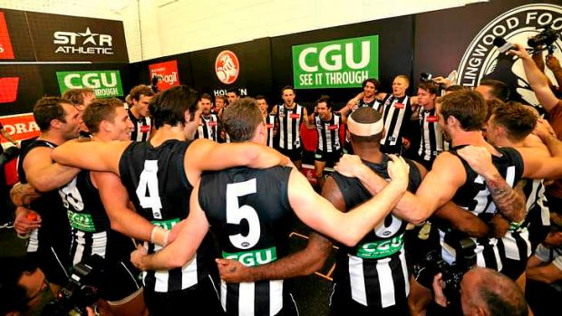 The Magpies belt out their song in the rooms following their win against Essendon.