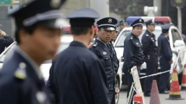 Security personnel guard the Malaysian embassy in Beijing on Friday as family members of passengers aboard gathered outside.