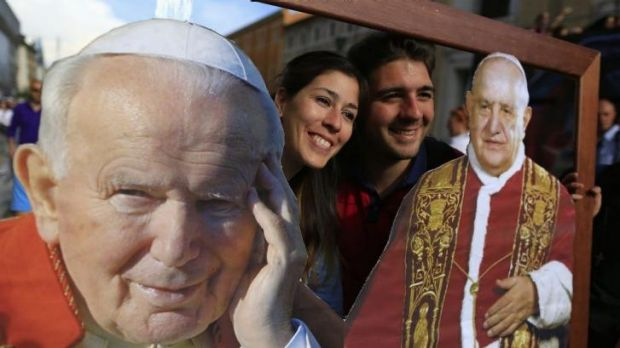 Two of the faithful pose with pictures of Pope John Paul II (L) and Pope John XXIII in front of St Peter's Square, in ...