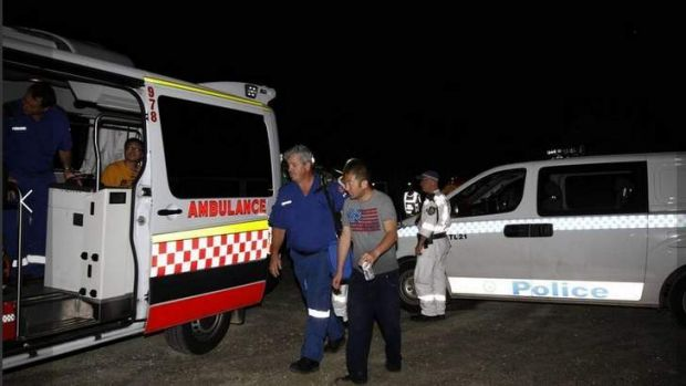 Rescue: One of the survivors is helped to an ambulance last night after the accident at Frazer Park.